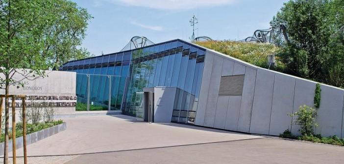Der dynamisch gestaltete Eingangsbereich mit großzügigen Verglasungen und markanten Sichtbetonflächen. - © Garten-Moser