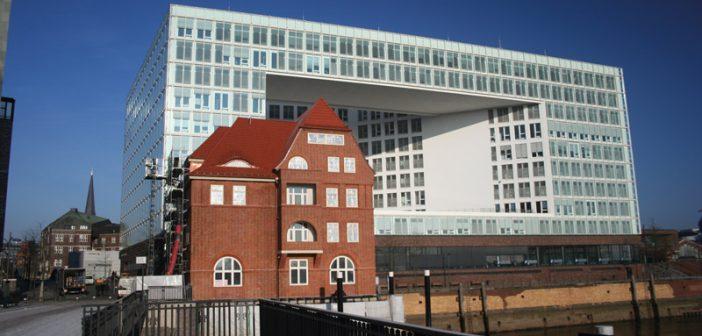 Sanierter Backsteinbau vor moderner Architektur.