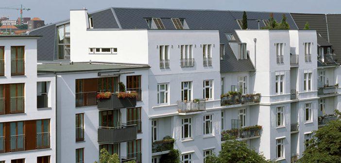 Die Repräsentationsgiebel der 1911 erbauten Gründerzeitgebäude in der Hamburger Isestraße wurden im Krieg zerstört. Die neue Dachaufstockung kommt ganz ohne historisierende Details aus. Glatte, blauschwarze Dachplatten und weiße Putzfassaden verleihen den Gebäuden heute eine moderne Erscheinung.